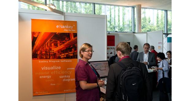 Martina Prox at ifu Hamburg stand, e!Sankey poster in background
